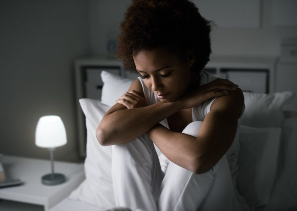 Sad depressed woman sitting in her bed late at night, she is pensive and suffering from insomnia